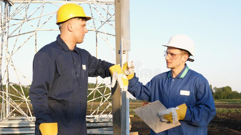 An electrician or builder and engineer, in a blue robe, in a yellow and white helmet, check the technical overview for strength, p. Repare electric poles, an royalty free stock image