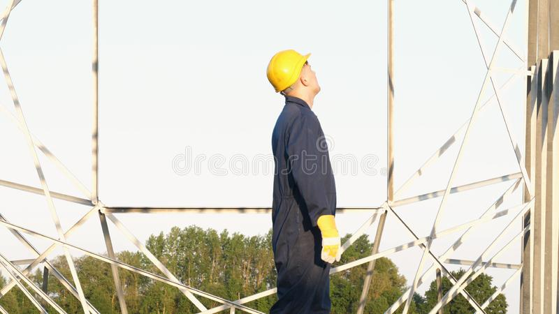 An electrician or builder and engineer, in a blue robe, in a yellow and white helmet, check the technical overview for strength, p royalty free stock photography