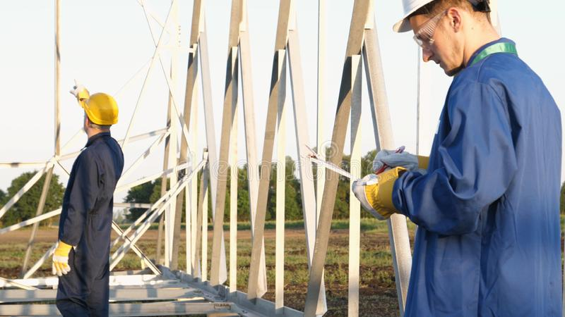 An electrician or builder and engineer, in a blue robe, in a yellow and white helmet, check the technical overview for strength, p. Repare electric poles, an stock photo