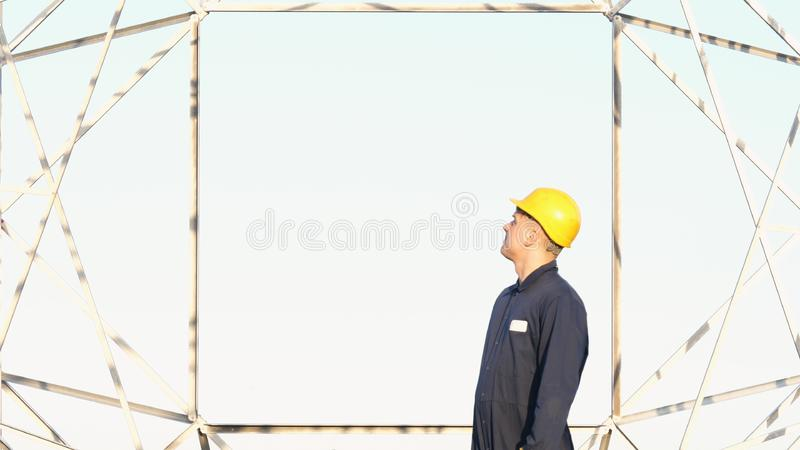 An electrician or builder and engineer, in a blue robe, in a yellow and white helmet, check the technical overview for strength, p stock image