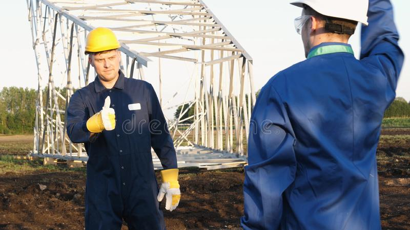 An electrician or builder and engineer, in a blue robe, in a yellow and white helmet, check the technical overview for strength, p stock photography