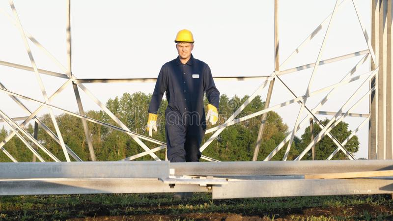 An electrician or builder and engineer, in a blue robe, in a yellow and white helmet, check the technical overview for strength, p stock photos