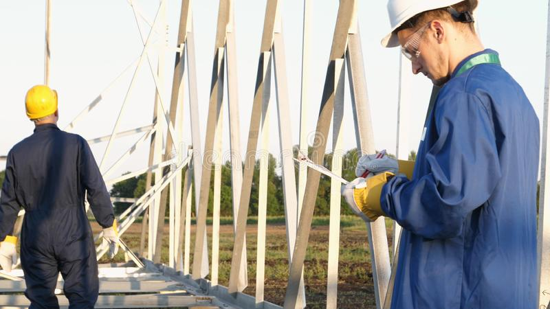 An electrician or builder and engineer, in a blue robe, in a yellow and white helmet, check the technical overview for strength, p. Repare electric poles, an stock images