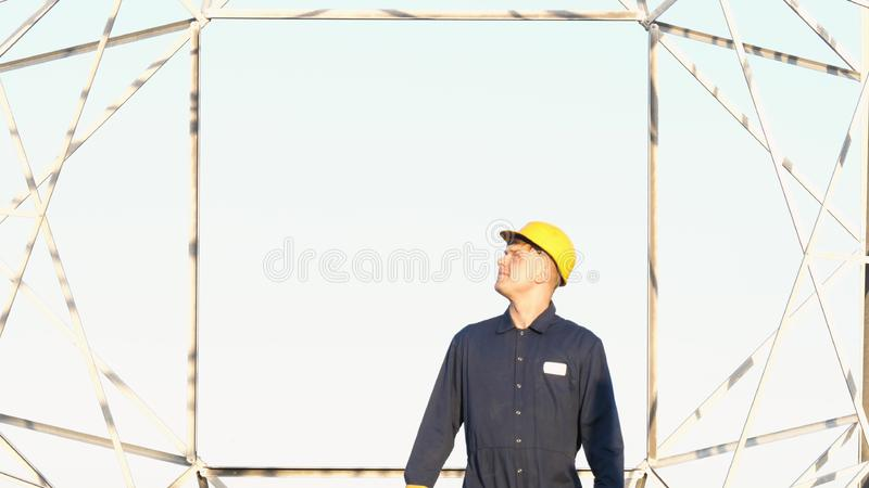 An electrician or builder and engineer, in a blue robe, in a yellow and white helmet, check the technical overview for strength, p. Repare electric poles, an stock image