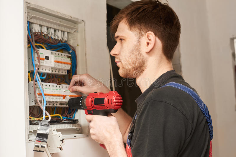 Electrician builder engineer screwing equipment in fuse box stock image
