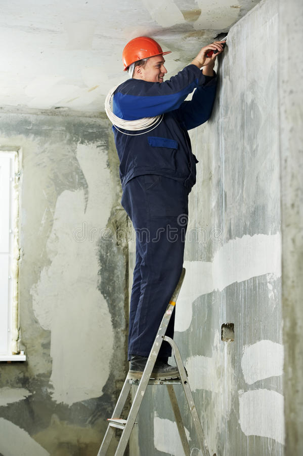 Electrician at cable wiring work. One electrician at work laying wiring cable stock photos