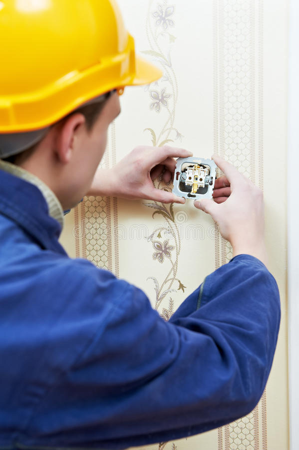 Electrician at cable wiring work. Electrician worker installing and light switch or power wall outlet socket royalty free stock image