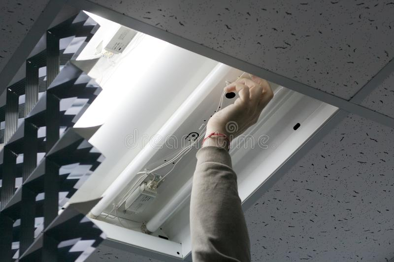 An electrician came to the office to check and repair the light. stock photo