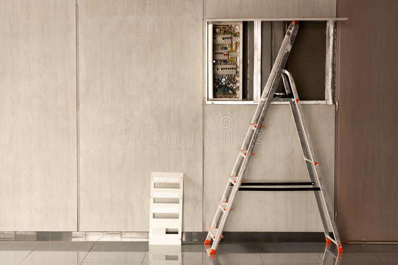 An electrician came to an office space to repair electricity in a room. Used stepladder for repair. royalty free stock photo