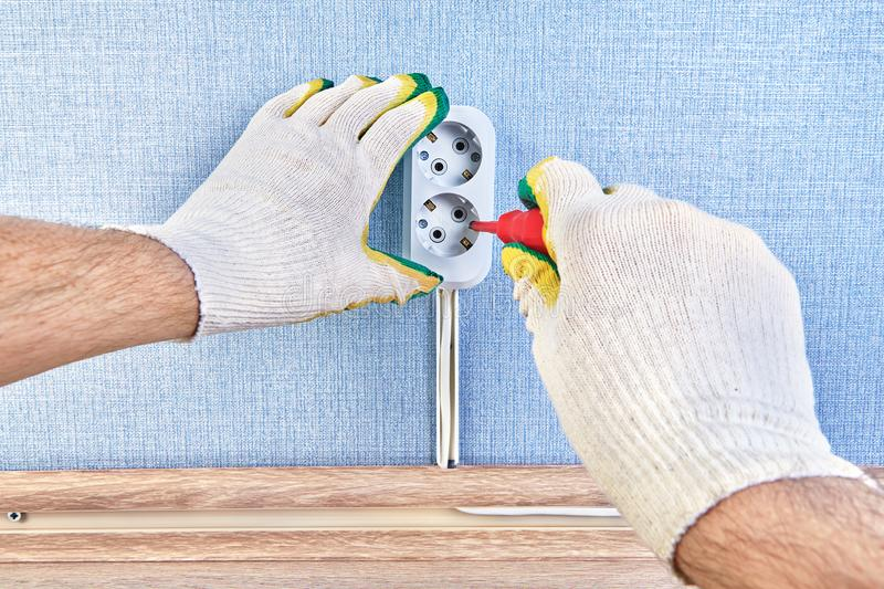 Electrician changes pattress box of wall outlet royalty free stock images
