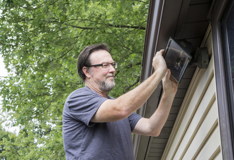 Electrician Changing Light Bulb In Exterior Light stock image
