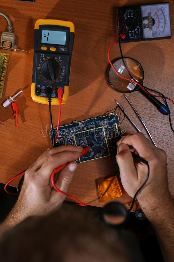 Electrician checking circuit board with multimeter stock images