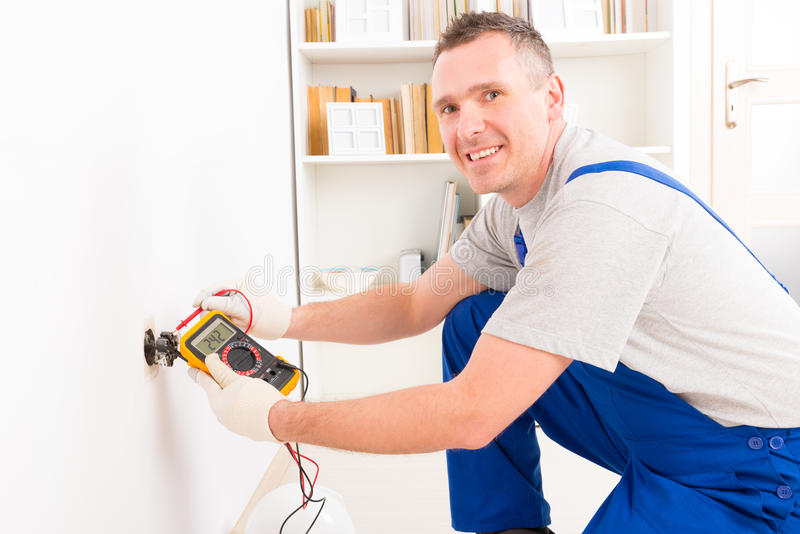 Electrician checking socket. Voltage with digital multimeter royalty free stock image