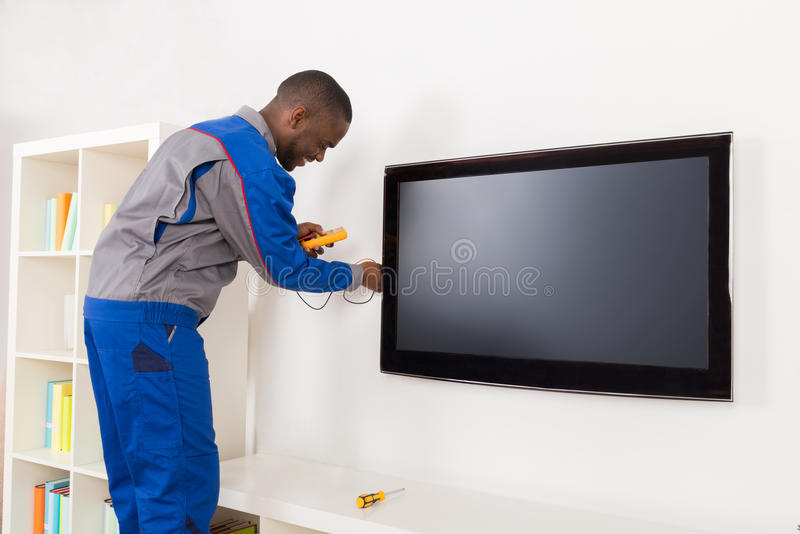 Electrician Checking Television With Multimeter royalty free stock photos