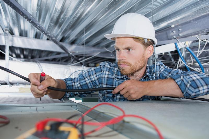 Electrician checking wiring in office royalty free stock photos