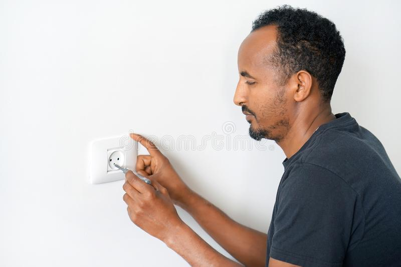 An electrician checks the voltage in the wall socket. Man electrician checks the presence of electrical voltage in the socket phase. Checking the voltage in the stock photography