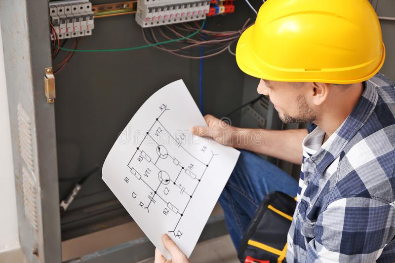Electrician with circuit diagram near distribution board stock photo