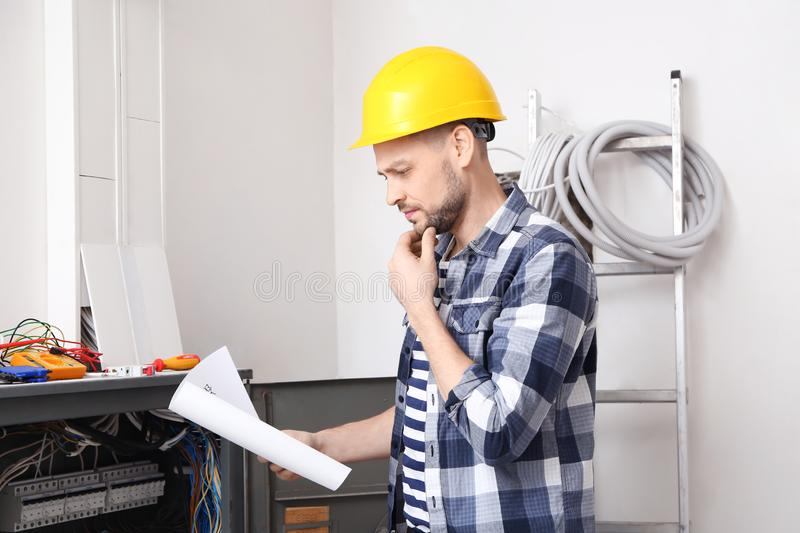 Electrician with circuit diagram near distribution board stock image