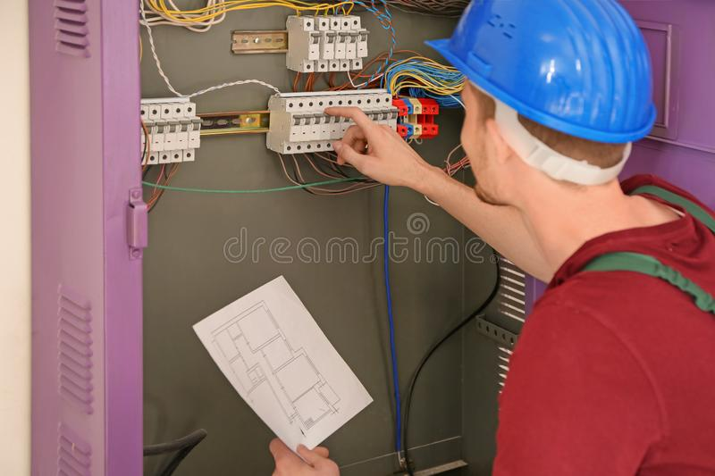 Electrician with circuit diagram repairing distribution board royalty free stock photography