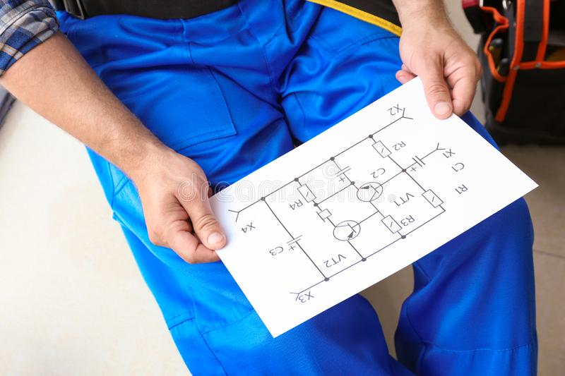 Electrician with circuit diagram sitting indoors royalty free stock image