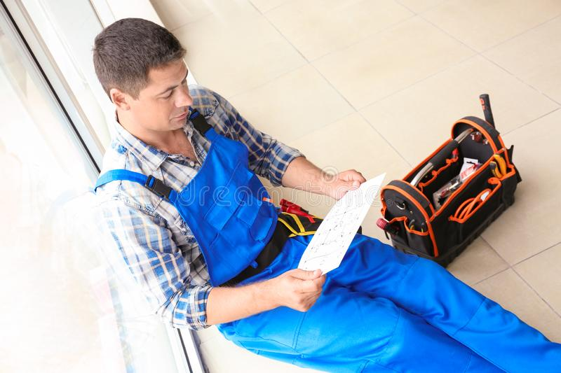 Electrician with circuit diagram sitting on windowsill indoors stock photography