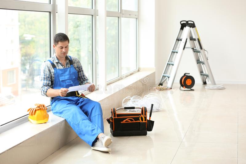 Electrician with circuit diagram sitting on windowsill in new empty apartment stock photo