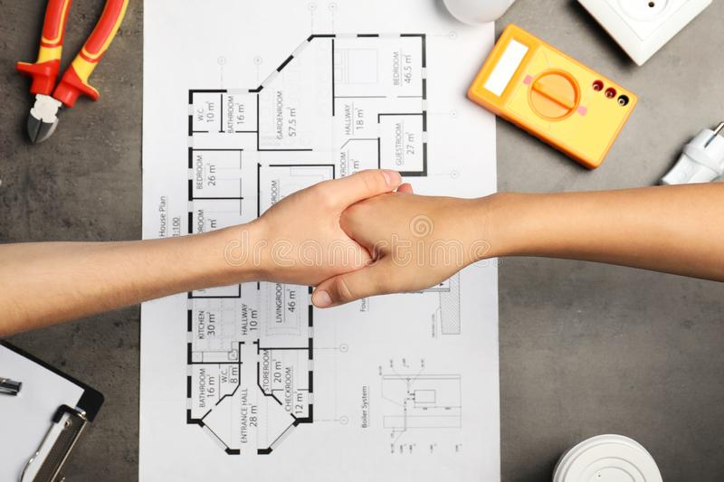Electrician and client shaking hands over table stock photos