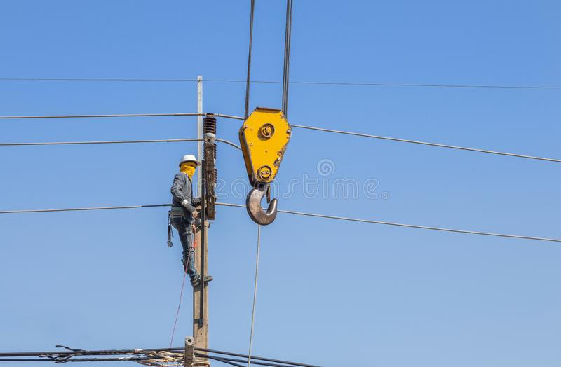 Electrician climbing work in the height on concrete electric power pole with big crane. On blue sky royalty free stock image