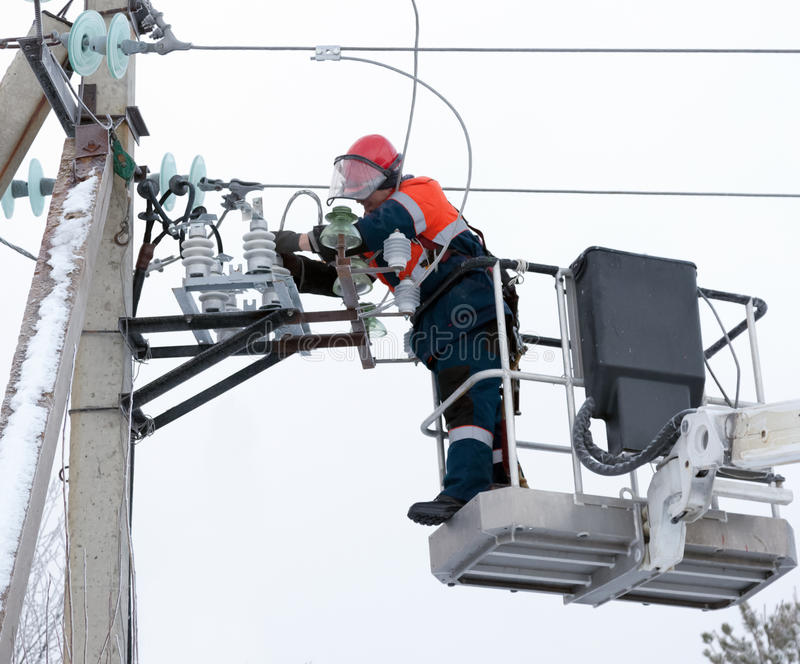 Electrician connect the wires to the line isolator stock images