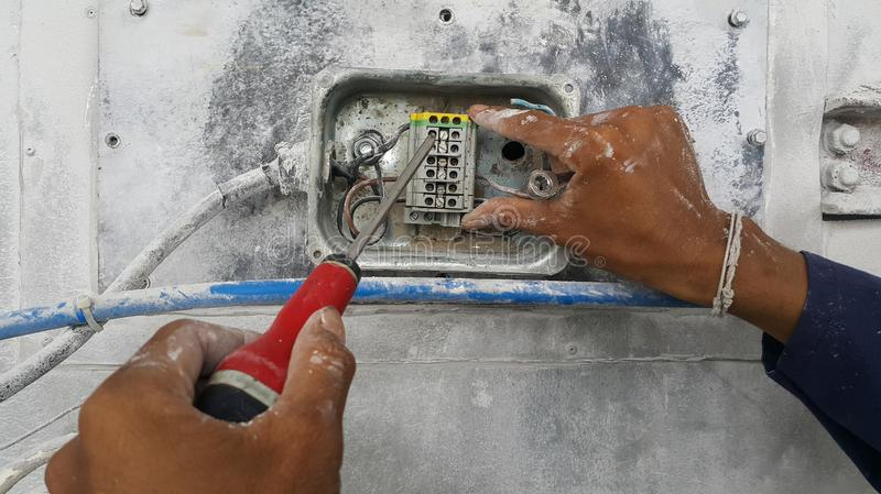 The electrician is connecting the power cable. To the connection point using a screwdriver royalty free stock photography