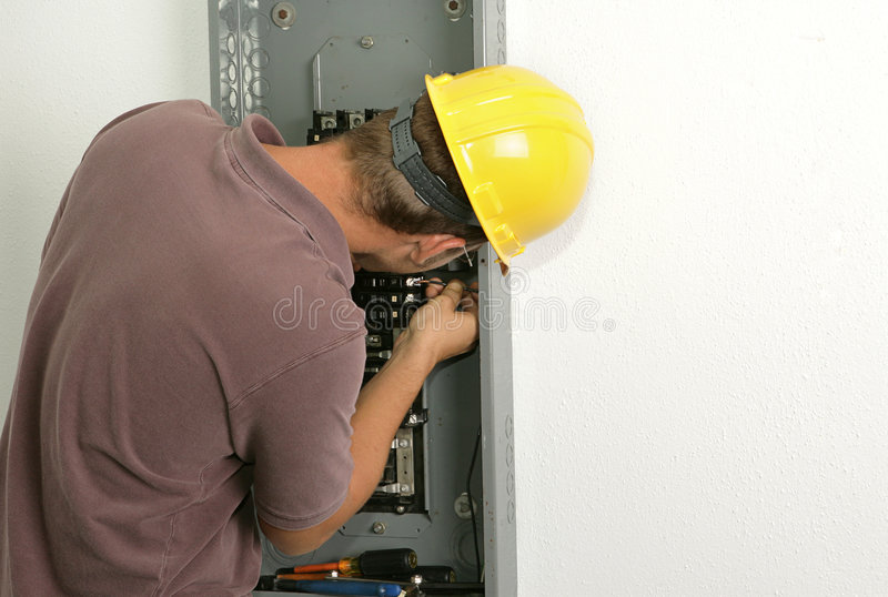 Electrician Connecting Wire. An electrician working on an electrical panel, connecting a wire to a breaker. Model is an actual electrician and all work performed royalty free stock photos