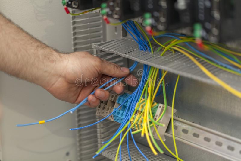 Electrician connecting wire on the control panel royalty free stock photography
