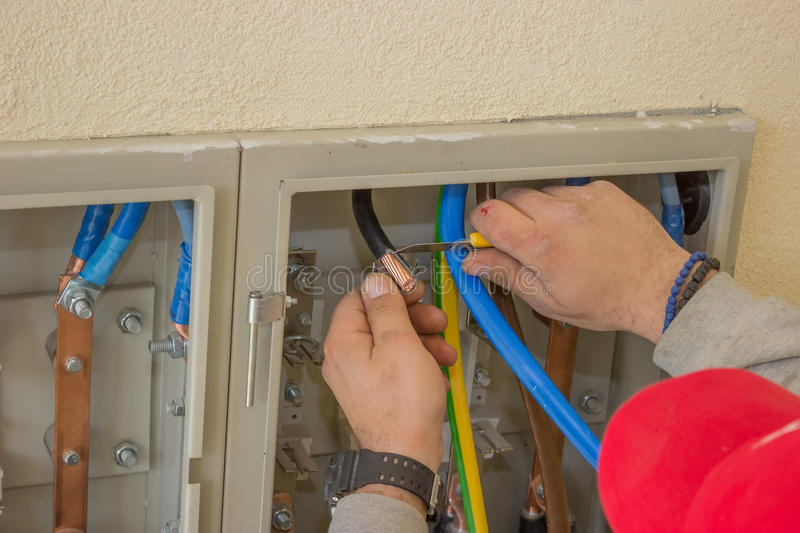 Electrician connecting wires in the electrical cabinet royalty free stock photo