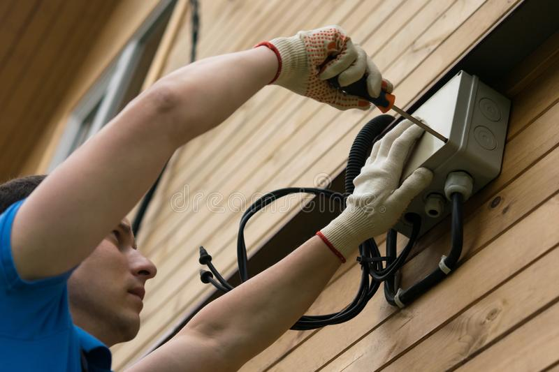 Electrician connects house to electricity, close-up royalty free stock photography
