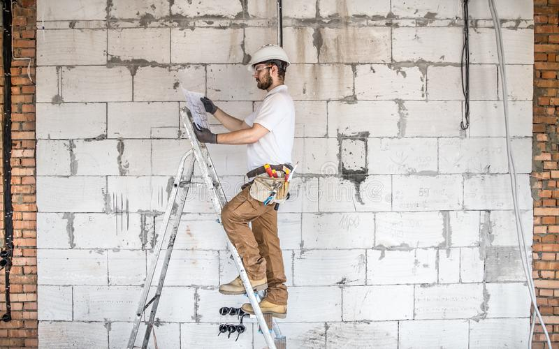 Electrician with construction tools, looking at drawings on the construction site.Repair and handyman concept. House and house reconstruction stock photo
