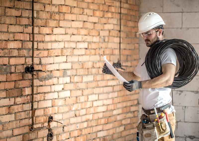 Electrician with construction tools, looking at drawings on the construction site.Repair and handyman concept. House and house reconstruction stock images