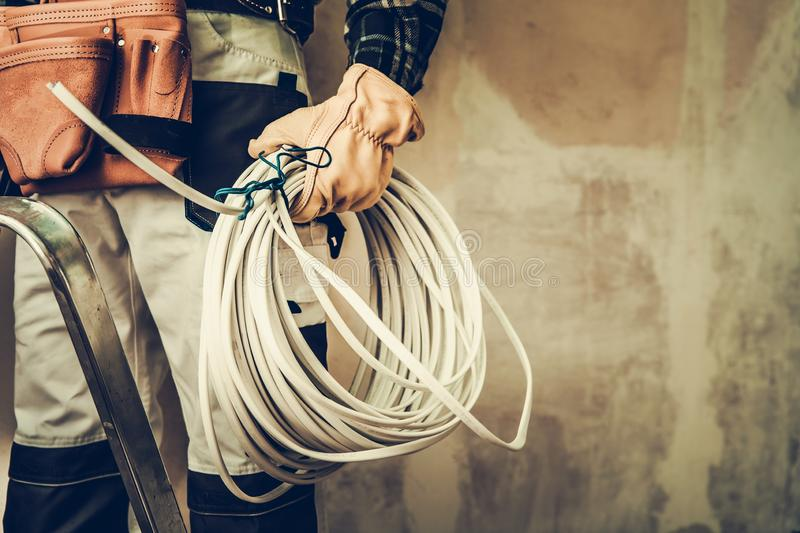 Electrician Contractor Cable. Electrician Contractor with Electric Cable Closeup Photo. Installing Whole New System stock image