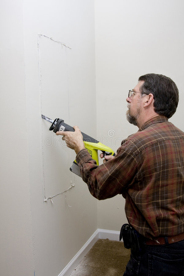 Electrician cutting access hole royalty free stock image