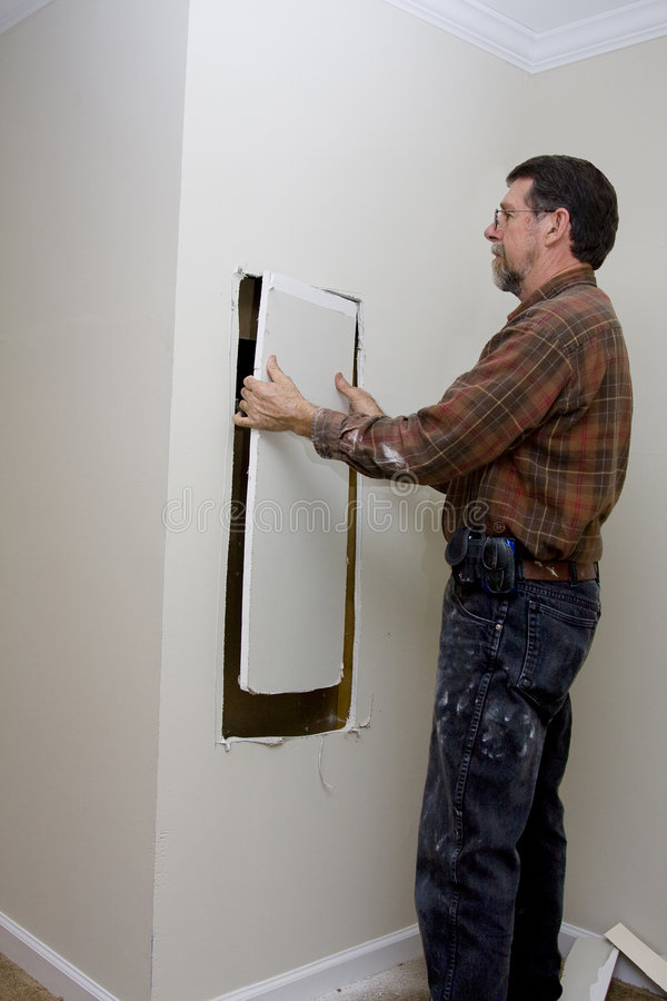 Electrician cutting access hole royalty free stock images