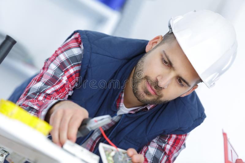 Electrician cutting red cable with cutters stock photos