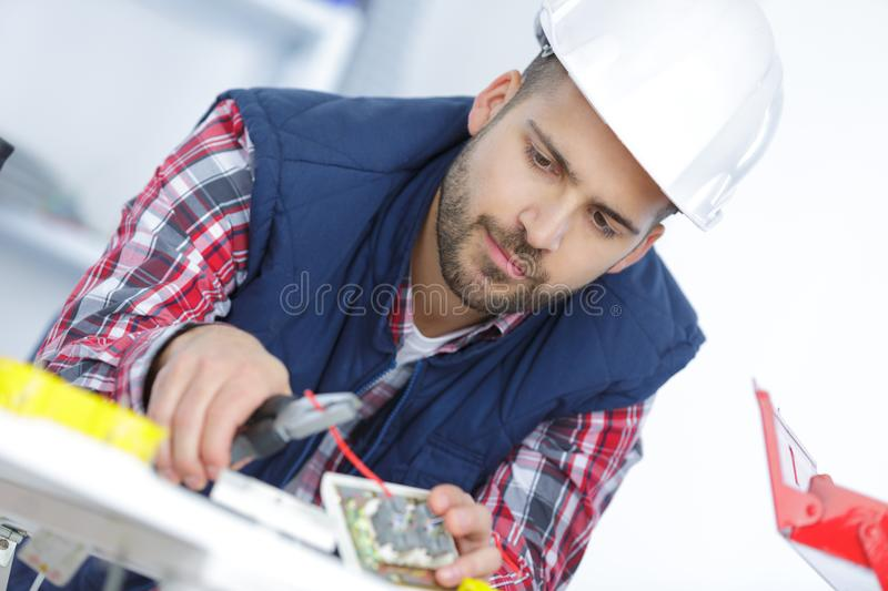 Electrician cutting wire with pliers stock images