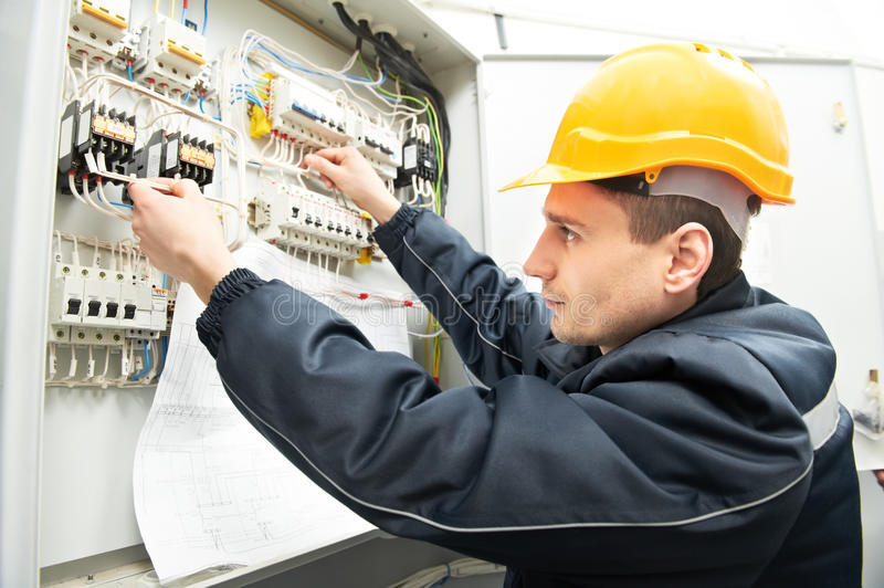 Electrician with drawing at power line box royalty free stock image
