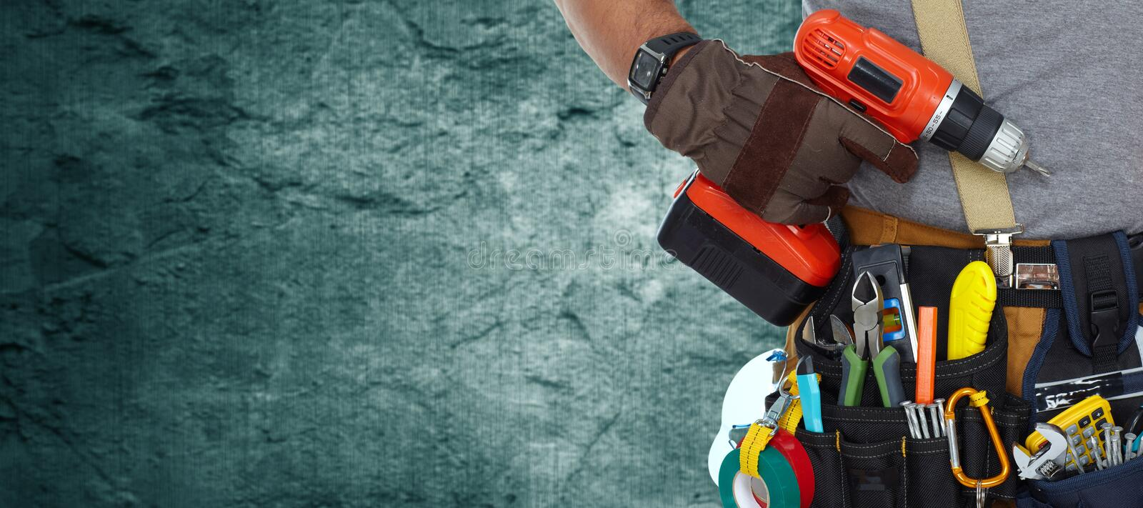 Electrician with drill. Builder handyman with construction tools on dark wall background royalty free stock photo