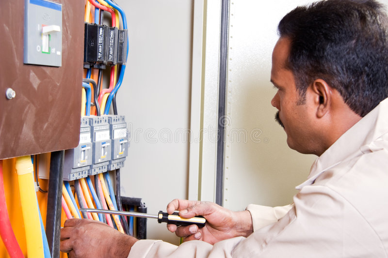 Electrician at electric panel. Electrician inspecting wires in electric panel royalty free stock photography