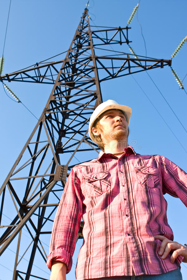 Electrician on an electricity pylon. Against blue sky stock image