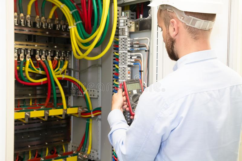 Electrician engineer with measuring tool works stock photography