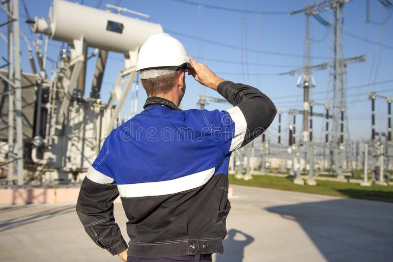Electrician engineer on power electric station look at industrial equipment. Technician in helmet on electro substation royalty free stock photography