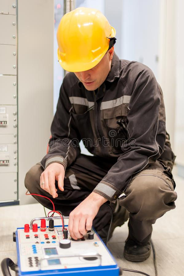 Electrician engineer tests system with relay test set equipment royalty free stock images