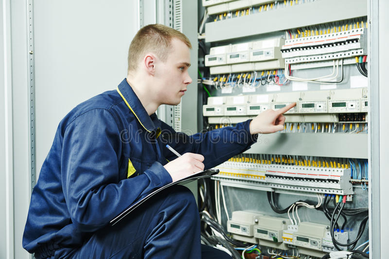 Electrician engineer worker. Inspector in front of fuseboard equipment in room royalty free stock image