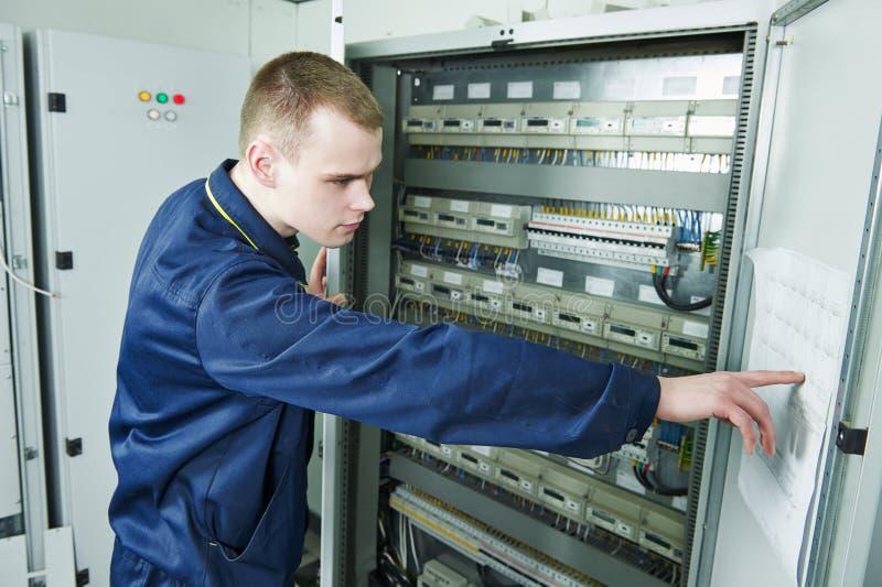 Electrician engineer worker. Inspector in front of fuseboard equipment in room stock images
